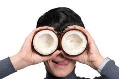 年轻女人藏品两一半在眼睛前面的椰子 免版税库存图片