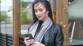 年轻女人藏品电话,看,微笑 长发在强风开发 股票视频