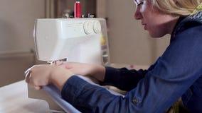 年轻女人裁缝在家工作,准备织品,开始缝合 缝纫机 股票视频