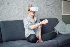 年轻女人观看的录影或使用与在头的VR玻璃 免版税图库摄影
