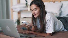 年轻女人谎言画象在床上在她的胃和谈话在电话,慢动作 股票录像