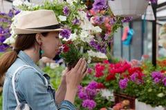 年轻女人购物在户外新都市花市场上,买和采摘从大品种五颜六色花卉 免版税库存图片