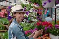 年轻女人购物在户外新都市花市场上,买和采摘从大品种五颜六色花卉 免版税库存照片