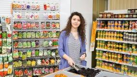 年轻女人购物在超级市场 免版税库存图片