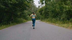 年轻女人赛跑者训练后面看法在夏天公园 健身女孩跑步室外 早晨连续概念 股票录像