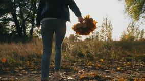 年轻女人赛跑通过有黄色枫叶花束的秋天公园在她的手上 女孩获得乐趣在五颜六色 股票录像