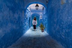 年轻女人通过舍夫沙万街道,蓝色镇漫步在摩洛哥,在墙壁和蓝色曲拱之间 库存照片