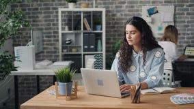 年轻女人雇员与膝上型计算机一起使用在完成工作的办公室在互联网 股票录像