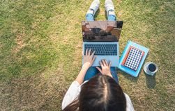 年轻女人顶视图偶然成套装备的使用膝上型计算机,当坐与数字片剂、笔记本和智能手机时的草 ?? 免版税图库摄影