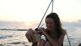 年轻女人风帆乘快艇并且使用智能手机-采取selfie 影视素材