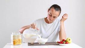 年轻女人食用一个早餐玉米片用牛奶和果子 免版税图库摄影