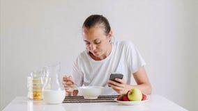年轻女人食用一顿早餐并且看在智能手机 免版税库存图片