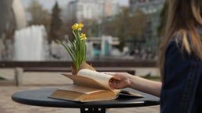 年轻女人饮用的咖啡,读书,生叶通过页在俯视喷泉的咖啡馆的一张桌上 影视素材