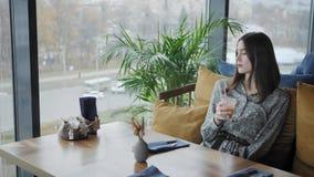 年轻女人饮用的汁液,bloging 在咖啡馆现代coworking的自由职业者工作 成功的人民,商人 影视素材