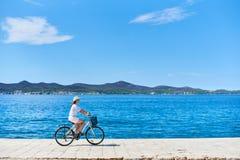 年轻女人骑马在海附近的城市自行车 库存照片
