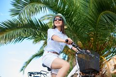年轻女人骑马在海附近的城市自行车 免版税库存照片