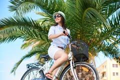 年轻女人骑马在海附近的城市自行车 库存图片