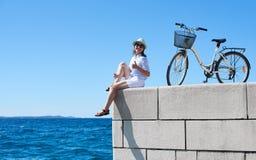 年轻女人骑马在海附近的城市自行车 免版税库存图片