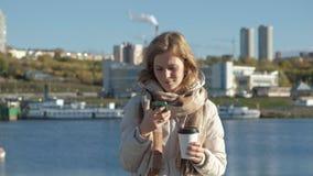 年轻女人,一件白色夹克的,在内河港,喝咖啡,用途电话,微笑,特写镜头 影视素材