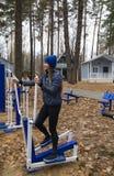 年轻女人,在体育similator的锻炼,自然,秋天,生活方式,森林 免版税库存图片