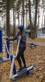 年轻女人,在体育similator的锻炼,自然,秋天,生活方式,森林 免版税库存照片