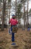 年轻女人,在体育similator的锻炼,自然,秋天,生活方式,森林 免版税图库摄影