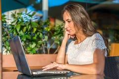 年轻女作家文字侧视图在她的膝上型计算机的,当坐在公园咖啡馆时 女孩键入的netbook户外 免版税库存图片