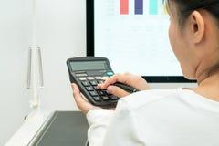 年轻女商人与计算器一起使用和计算机桌面和笔在现代工作表上 免版税库存照片
