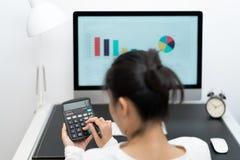年轻女商人与计算器一起使用和计算机桌面和笔在现代工作表上 库存照片