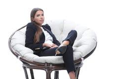 年轻女商人在一把圆的椅子放松 图库摄影