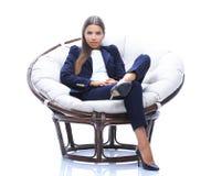 年轻女商人在一把圆的椅子放松 库存照片