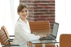 年轻女商人在她的书桌在办公室,运作坐便携式计算机 免版税库存图片