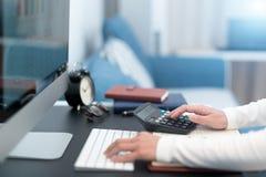 年轻女商人在家与在现代工作表办公室的计算器和计算机桌面一起使用 库存图片