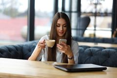 年轻女商人在看智能手机屏幕的餐馆 小姐饮用的热奶咖啡 免版税库存图片