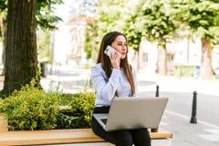 年轻女商人室外谈话坐电话,当研究膝上型计算机时 库存图片