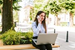 年轻女商人室外谈话坐电话,当研究膝上型计算机时 免版税图库摄影