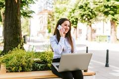 年轻女商人室外谈话坐电话,当研究膝上型计算机时 免版税库存照片