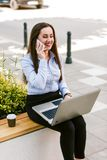 年轻女商人室外谈话坐电话,当研究膝上型计算机时 图库摄影