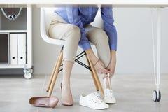 年轻女商人更换由于她的鞋子疲劳 免版税库存照片