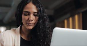 年轻女商人饮用的茶和观看的录影在膝上型计算机在现代办公室 股票录像