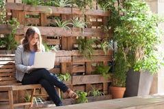年轻女实业家与在一条长凳的膝上型计算机一起使用与计划 免版税库存图片