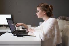 年轻女实业家凝视屏幕 有玻璃工作的美丽的女孩在家与膝上型计算机 免版税库存照片
