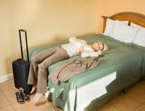 年轻女实业家分发睡着在旅馆床上 库存图片