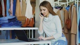 年轻女实业家在手机与膝上型计算机一起使用并且谈话在她的商店 衣裳和顾客在背景中 股票录像