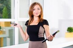 年轻女实业家在拿着片剂和智能手机有任务名单的现代明亮的办公室 文本的空位 图库摄影