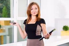 年轻女实业家在拿着片剂和智能手机有任务名单的现代明亮的办公室 文本的空位 免版税库存照片