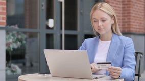 年轻女实业家坐的网络购物失败室外