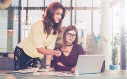 年轻女实业家帮助工作的一个同事 配合,群策群力 库存照片