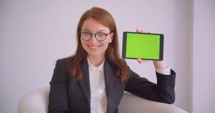 年轻女实业家特写镜头画象玻璃的使用片剂和显示绿色色度对照相机的关键屏幕 股票录像