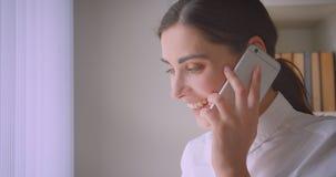 年轻女实业家特写镜头画象看一看电话谈的通过窗口在办公室书架  影视素材
